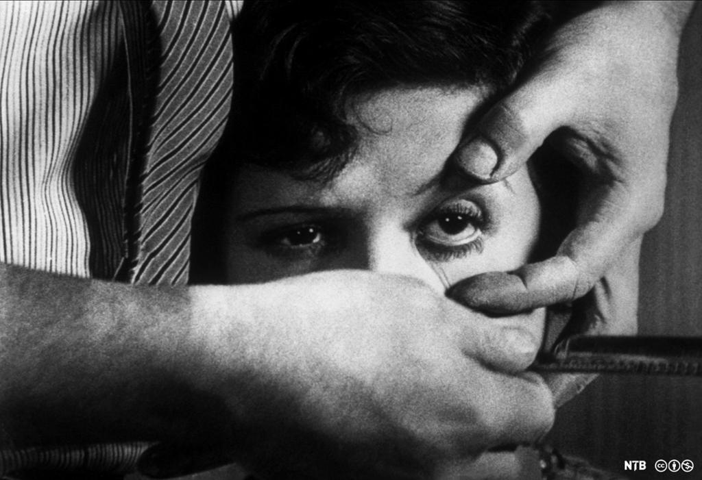 Nærbilde av hodet til en kvinne. En mann holder henne bakfrag og sperrer opp et av øynene hennes med den ene hånda. I den andre hånda holder han opp en barberkniv. Svart-hvitt-foto.