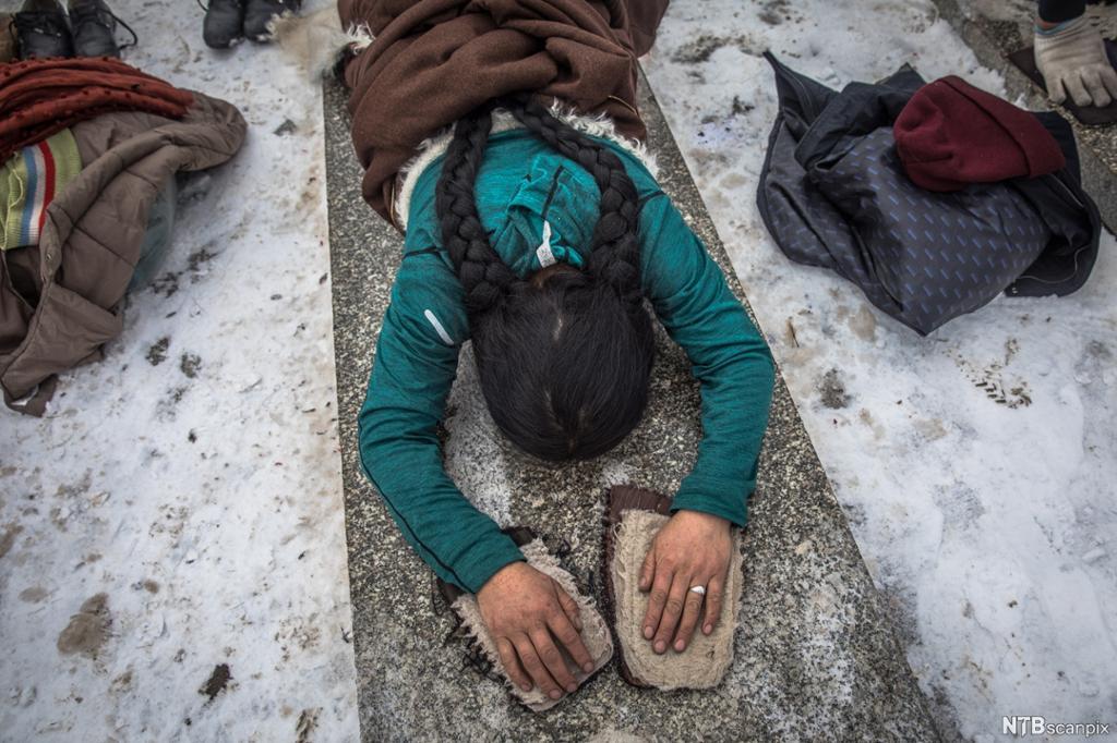 Kvinne ligger med ansiktet mot bakken og hendene frem. Foto.