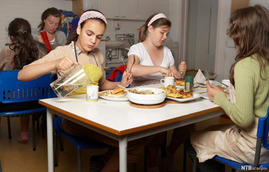 Elevar sit rundt bord og et mat. Foto.