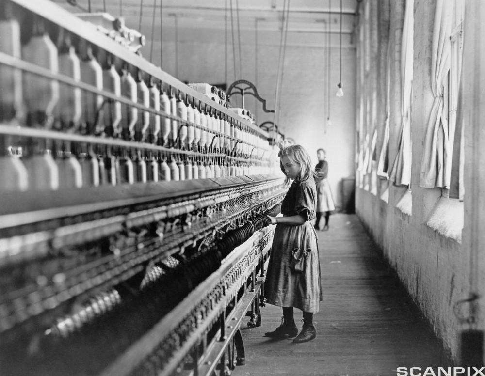 En ung jente i arbeid på et bomullsspinneri i Nord-Carolina i 1908. Foto.