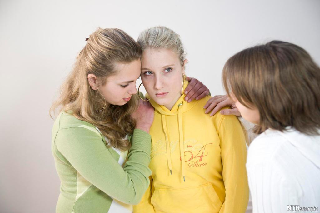 Ei ung jente i gul genser får trøst av to venninner. Den ene holder rundt henne, og den andre holder hånda på skulderen hennes. Foto.