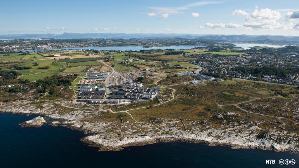 Flyfoto av et boligfelt som ikke ligger så langt fra havet. I bakgrunnen er det landbruksområder til venstre og mer tettbygde strøk til høyre. Foto.