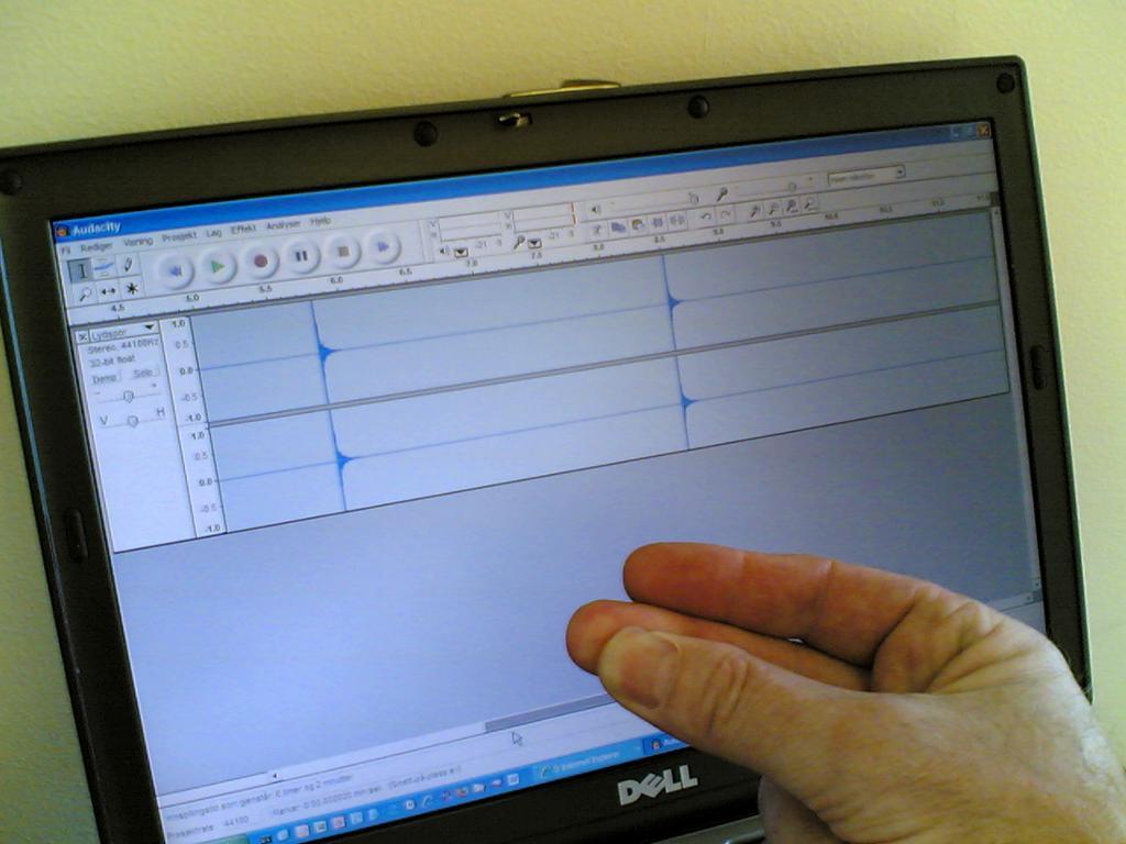 PC-skjerm og ei hand som knipser. Foto.