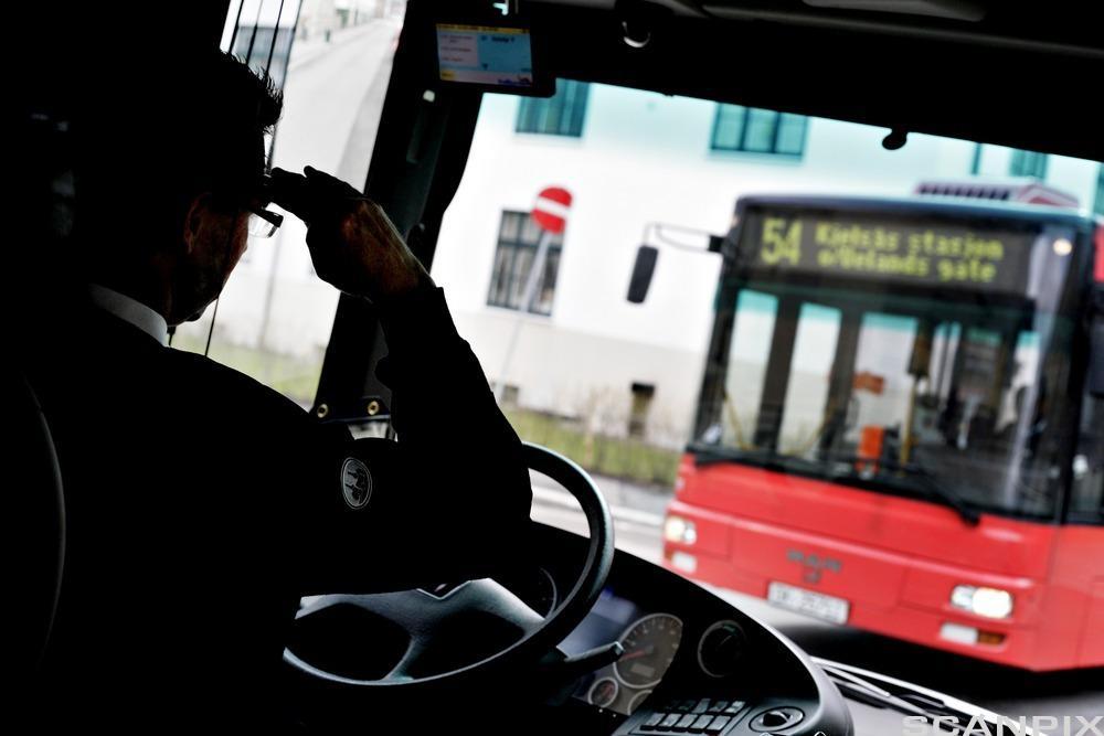 Bussjåfør bak rattet. Foto.
