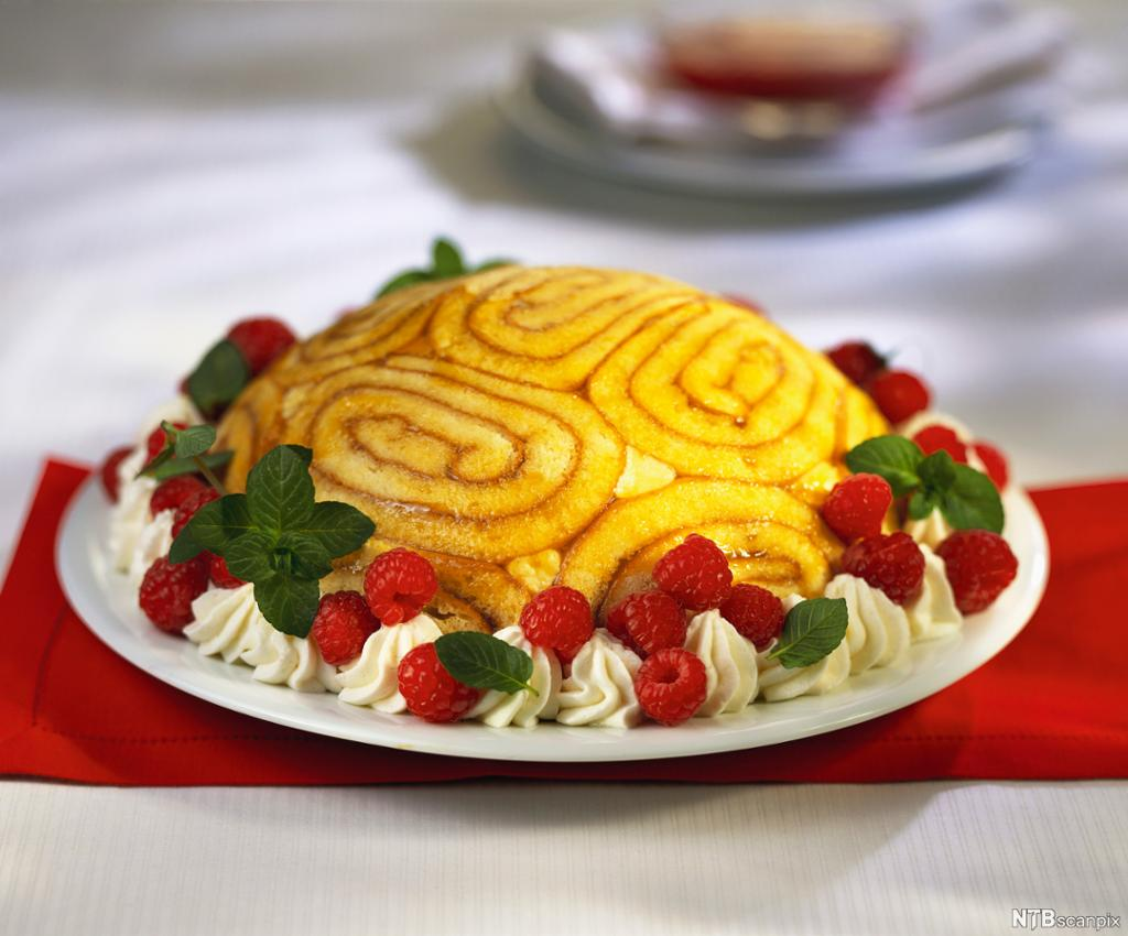 En charlotte russe-kake pynta med kremdotter, friske bringebær og mynteblader. Foto.