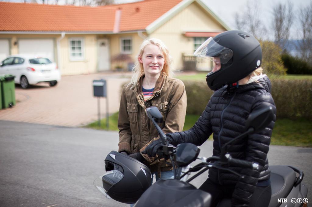 Jente på moped snakkar med ei anna jente som held ein mopedhjelm i hendene. Foto.