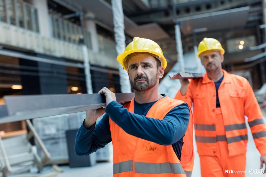 To bygningsarbeidere bærer metallarbeid. Foto.