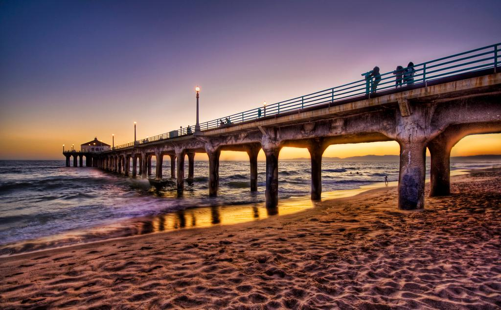 Strand og bro i solnedgang. Foto.