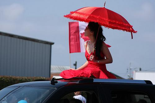 Lady dressed in red riding on the top of a car with an umbrella. Photo.