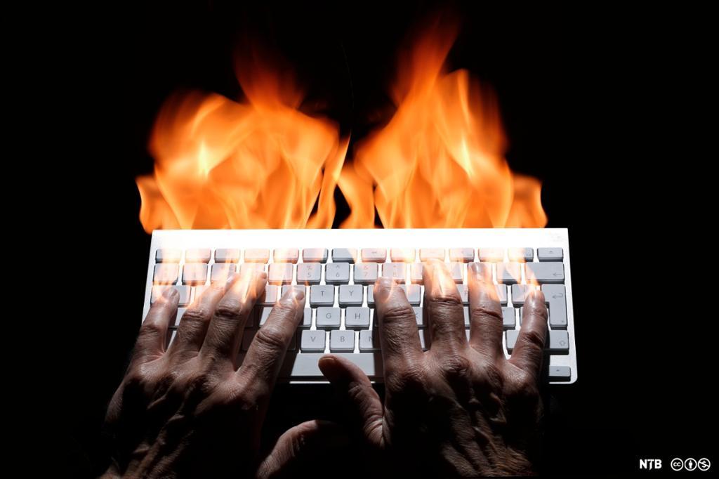 To hender skriver på et tastatur i et bekmørkt rom. Det står høye flammer opp av fingrene. Foto.