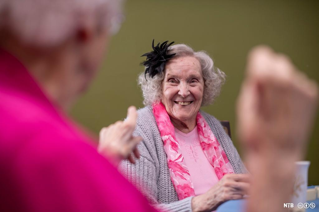 Eldre dame som smiler. Hun har rosa skjerf, grå jakke og en stor, svart blomst i håret. I forgrunnen ser vi en annen eldre kvinne med rosa klær, hun peker på dama som smiler. Foto.