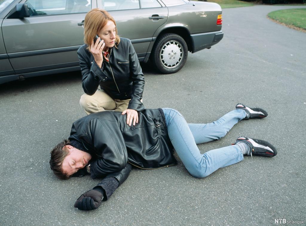 En mann er lagt i sideleie på asfalten foran en bil. En kvinne støtter ham og snakker i telefonen. Foto.
