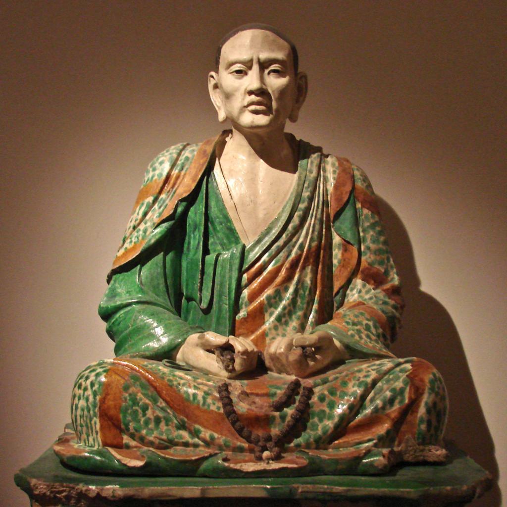 Mann sitter i lotusstilling iført grønn og rød kappe. Holder et kjede i hendene. Skulptur.