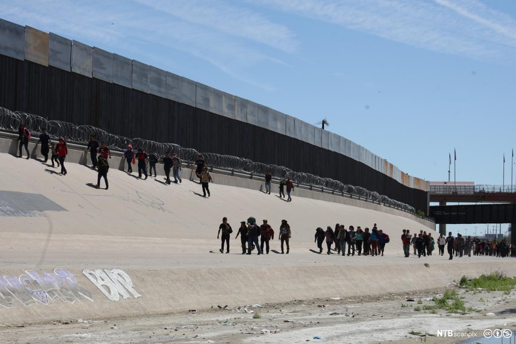 Et fotografi av meksikanske migranter på vei inn i USA.