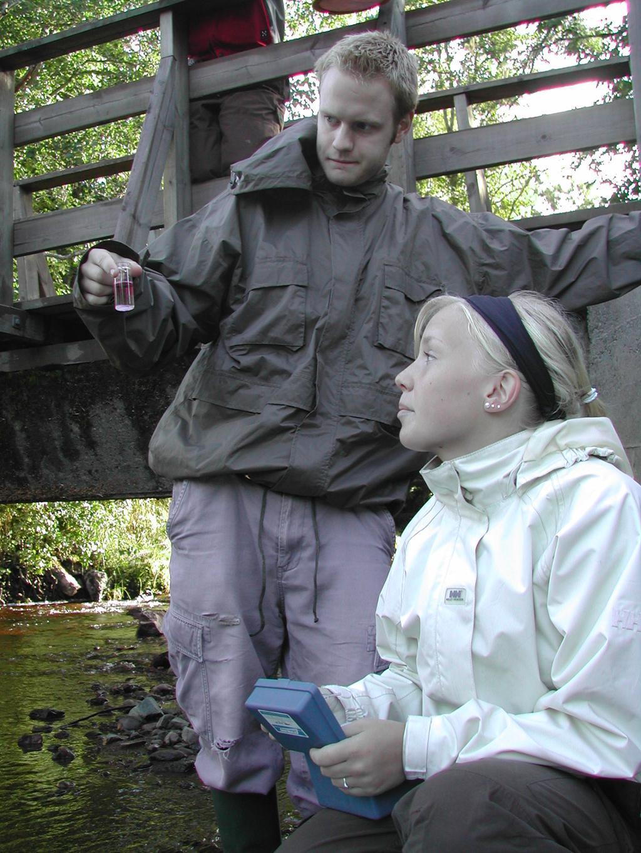 Gutt og jente vurderer vannprøve i elv. Foto.