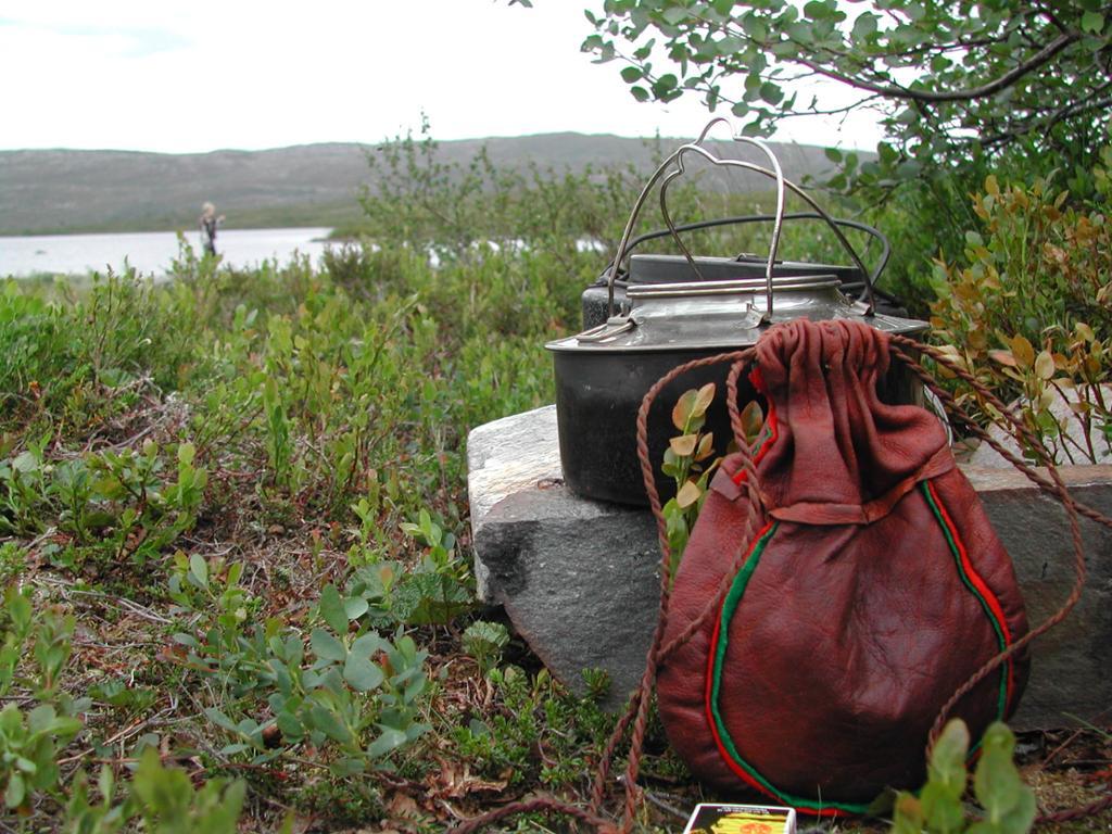 Kaffikjele på bålet i skogen, med ein skinnpose ved sidan av. Foto