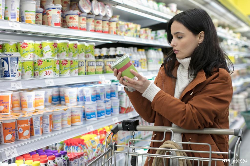Ung kvinne i daglegvarebutikken. Ho står ved ei handlevogn og ser på emballasjen til ein yoghurt som ho har teke ut frå hylla. Foto.