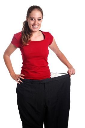 En tynn dame som har på seg en altfor stor herrebukse. Foto