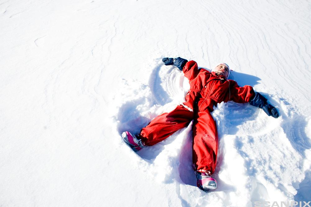 Et barn ligger på ryggen i snøen. Foto.