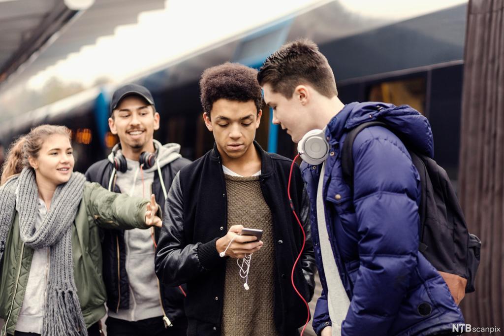 Fire venner av ulike etnisk bakgrunn står sammen på en t-banestasjon. Foto.