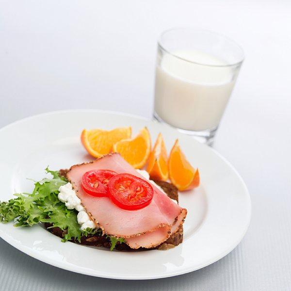 Tallerken med brødskiver og et glass melk til. Foto.