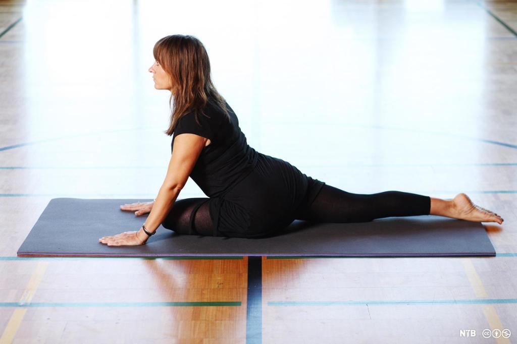 Kvinne ligger på en yogamatte og strekker ut. Foto.