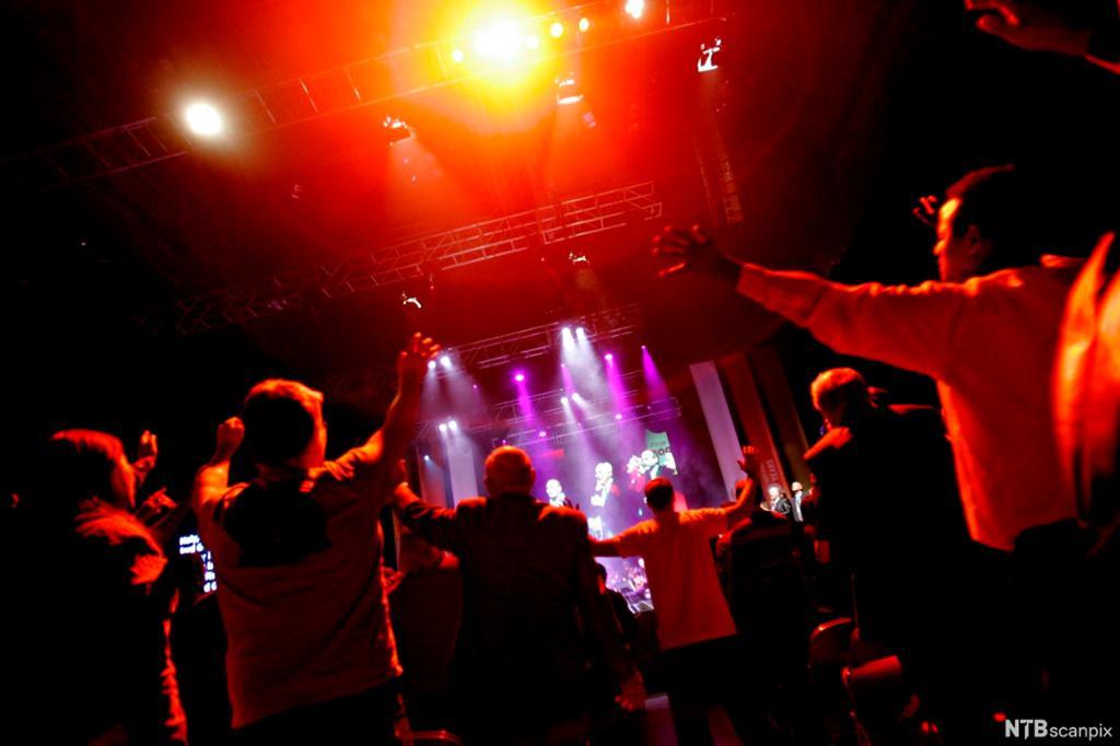 Forsamling står vendt mot en scene og strekker armene i været. Foto.