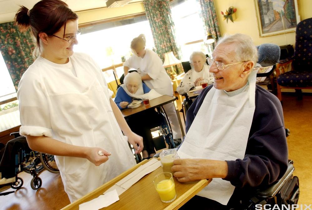 Helsefagarbeider og beboer på sykehjem. Foto.