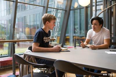 To unge menn som spiser lunsj i kantina mens de snakker sammen. Foto.
