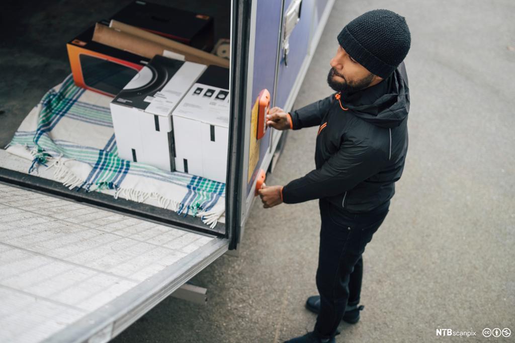 Sjåfør åpner bakluke på lastebil med betjeningspanel. foto.