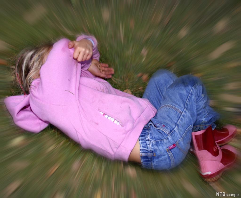 Ei lita jente ligger på gresset. Hun har på seg olabukse, rosa hettejakke og rosa og røde støvler. Hun holder armene foran ansiktet som om hun beskytter seg selv. Bildet er tatt ovenfra, og det er brukt effekter i bildet som illustrerer bevegelse rundt henne. Foto.