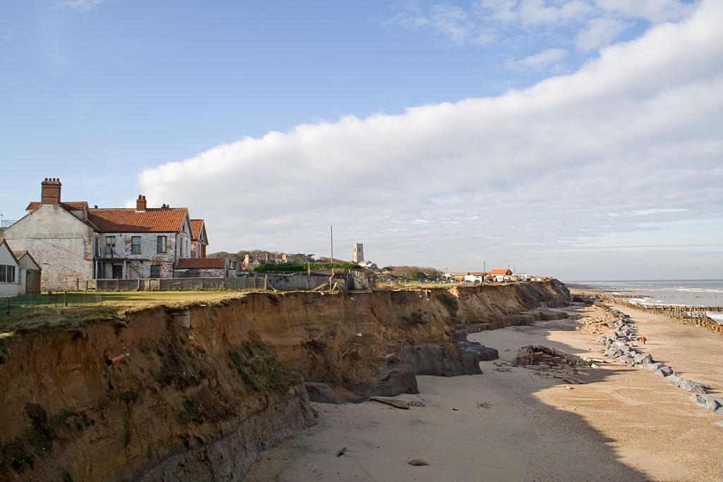 Kyst hvor hus er truet av havet.