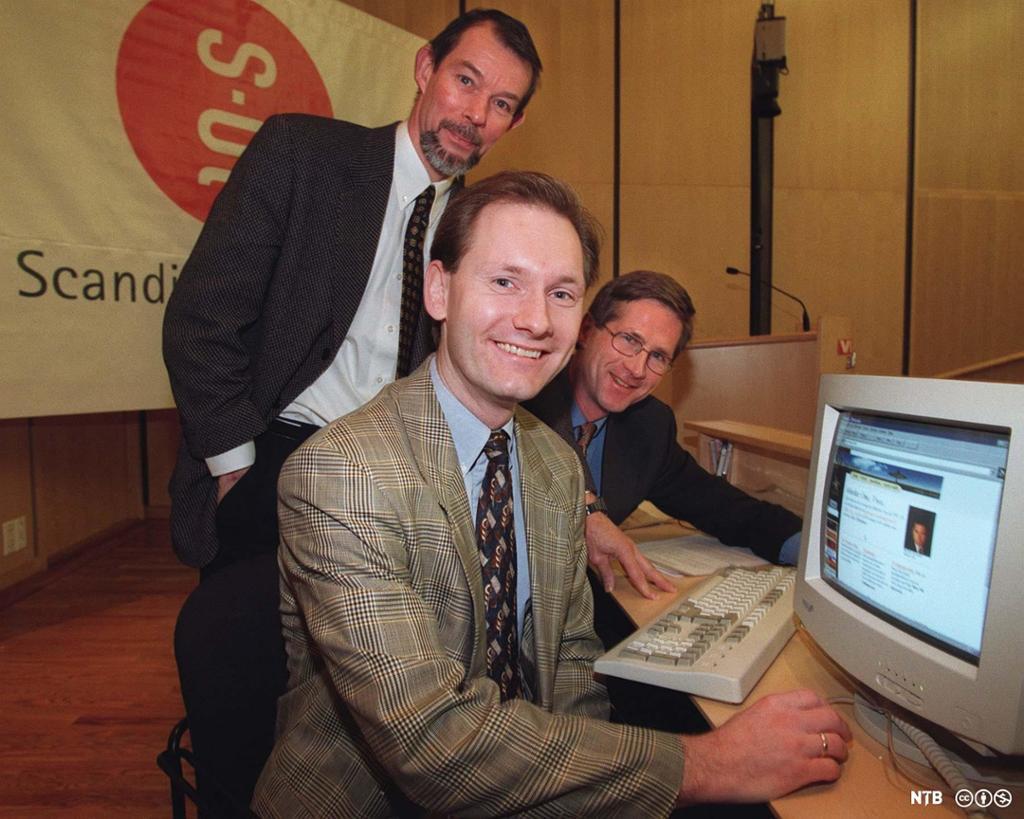 Tre dresskledde menn smiler foran en gammeldags PC. Foto.