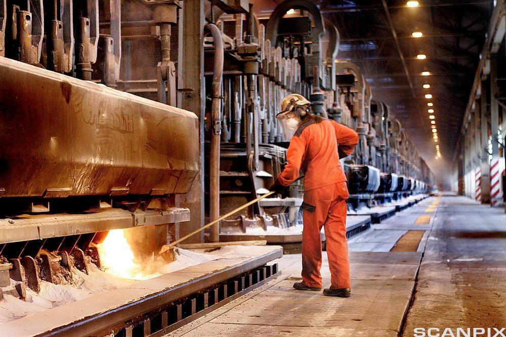 Arbeider i hjelm og kjeledress ved åpning til smelteovn, Hydro Aluminium. Foto.
