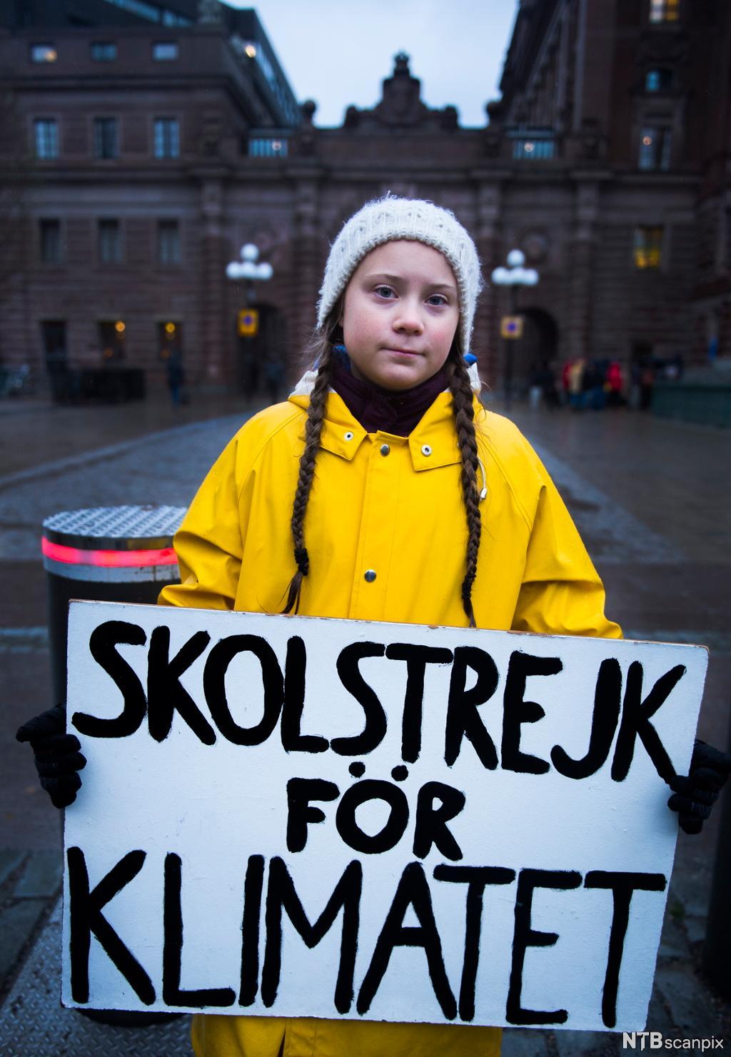 """Portrett av Greta Thunberg som held ein plaket med """"Skulestreik for klimaet"""" framom den svenske Riksdagen. Foto."""