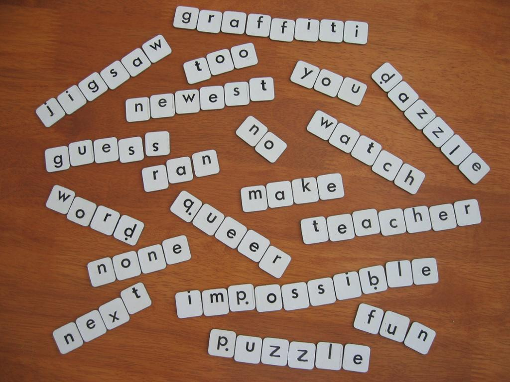 Pieces with letters forming words on a table. Photo.