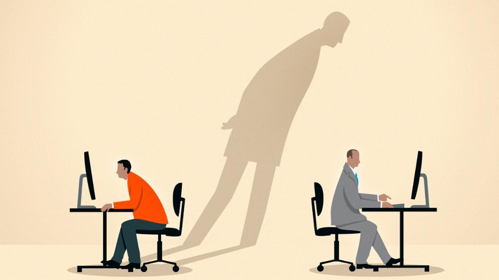 Å stjele en annen sin idé. Skyggen av en mann ser over skulderen på en som jobber på en PC. Foto