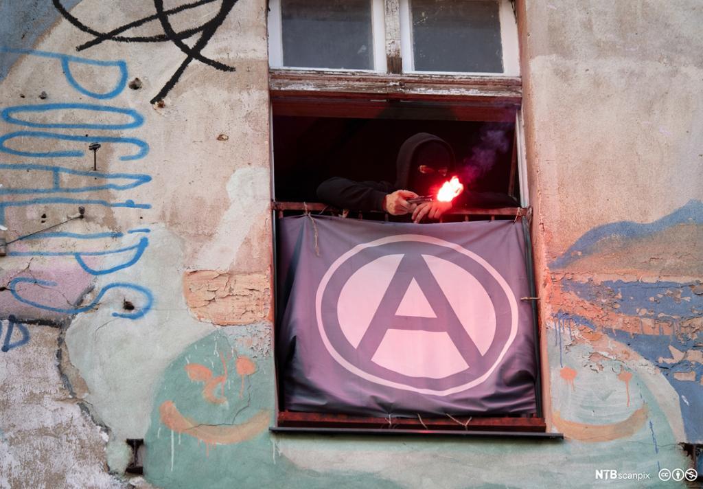 Mann som holder pyroteknikk i vindu drapert med en A for anarkisme. Fra 1. mai-demonstrasjon i Friedrichshain, Berlin, 2019. Foto.