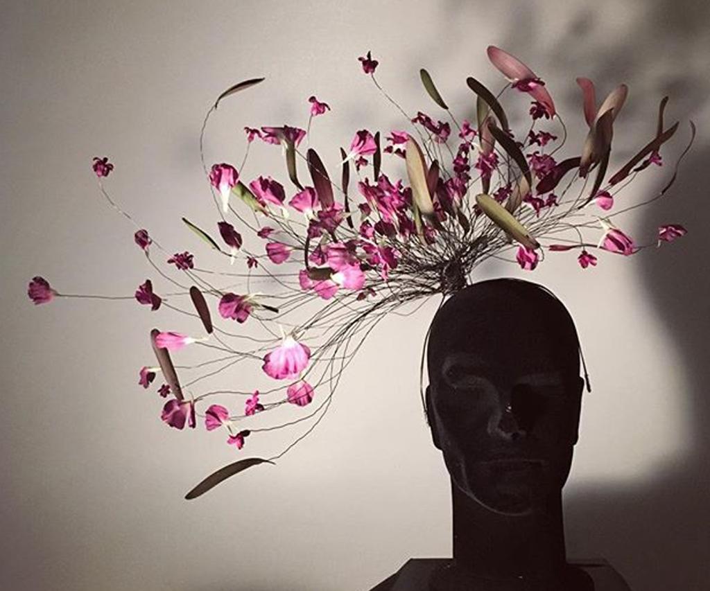 Byste med et hodeplagg laget av ståltråder og blomster. Foto.