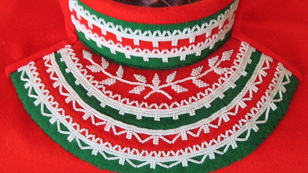 Barmklede i rødt og grønt, dekorert med hvite perler. Foto.