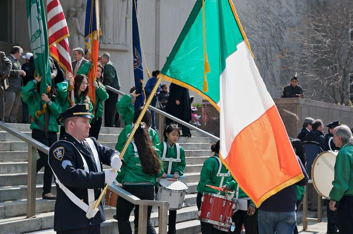 Man standing proudly with the irish flag. Photo.