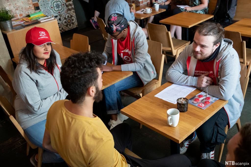 Tre personer fra sommerpatruljen til LO med LO-caps og t-skjorter snakker med en deltidsansatt på en arbeidsplass. Foto.