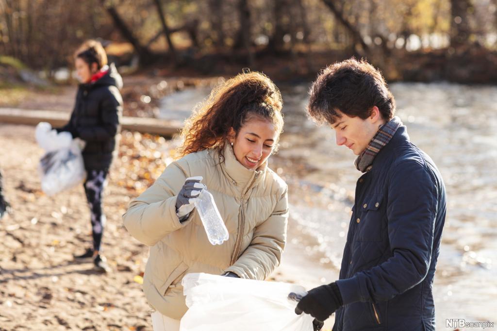 Ung gutt og ung jente plukker plast på ei strand. Foto.