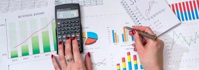 En kvinne jobber med kalkulator og mange ulike grafer og diagrammer. Foto.