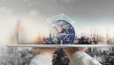 To hender balanserer et nettbrett horisontalt. Opp av nettbrettet stiger en jordklode omkranset av et nettverk av hvite, lyse striper. I bakgrunnen ser vi et skyskraperlandskap. Foto og digital illustrasjon.