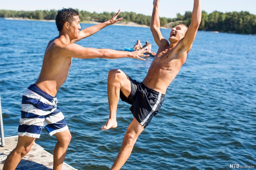 En gutt dytter en annen smilende gutt ut i vannet. Foto.