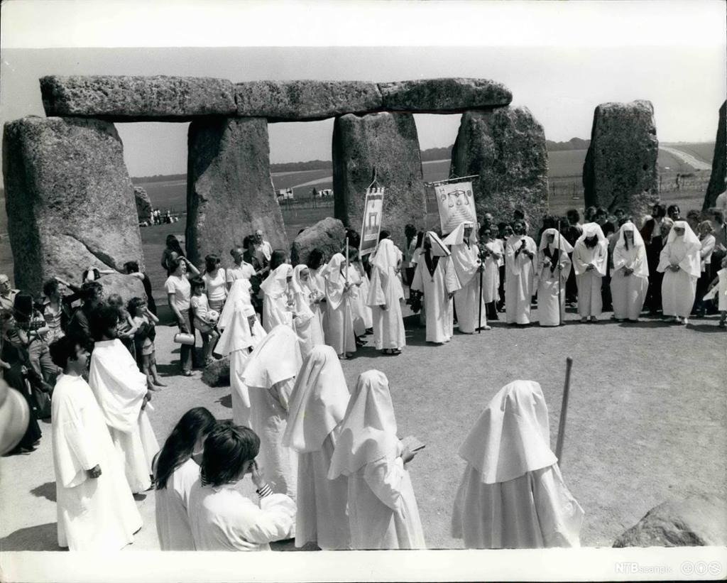 Mennesker kledd i hvite kapper står i en stor ring ved Stonehenge i England. Svart-hvitt. Foto.