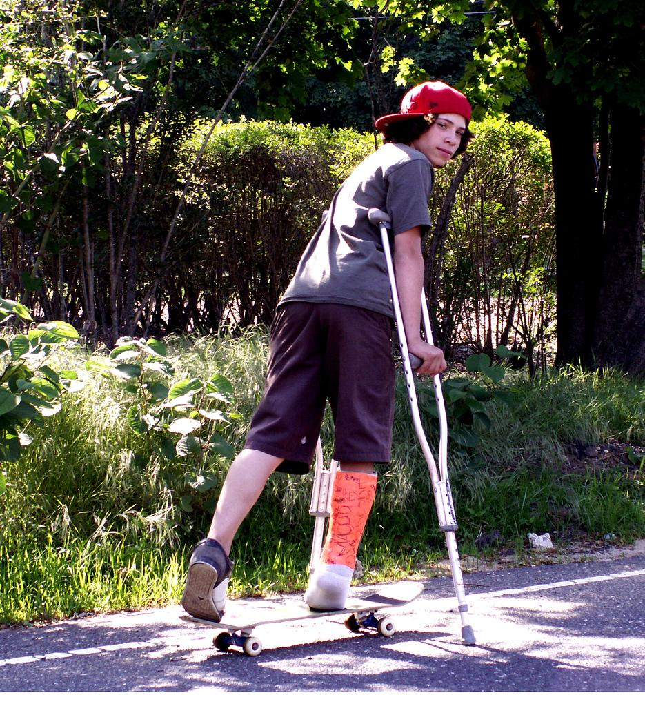 Gutt med krykker på skateboard. Foto.