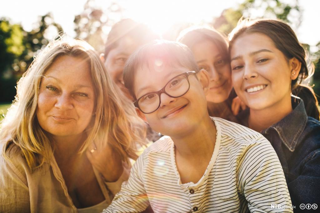 Nærportrett av smilende familie i en park. Foto.