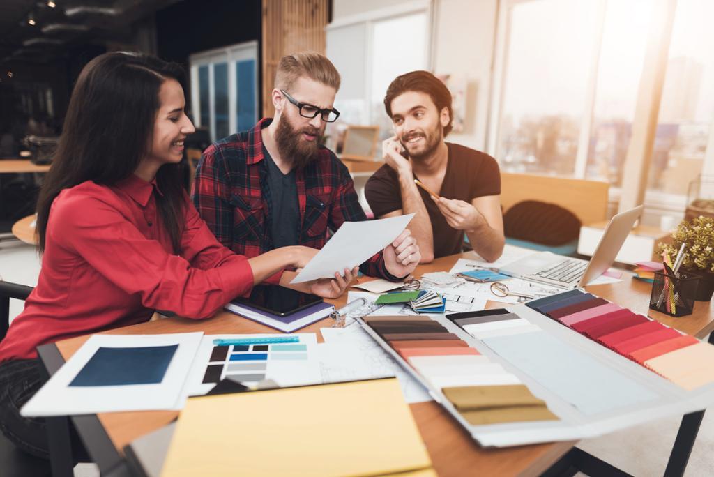 Tre designere diskuterer fargevalg og skisser rundt et bord i et kontorlandskap. Materialprøver, notatbok, papir, penner og Mac ligger på bordet. Foto.